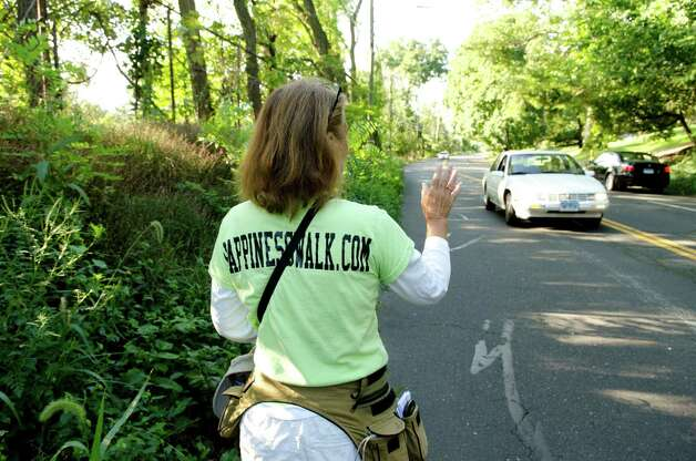 Paula Francis, 54, of Montpelier, VT, waves to a motorist as she walks along Stillwater Avenue in Stamford on Sunday, Sept. 16, 2012. Francis and her walking partner Linda Wheatley left Stowe, Vermont on August 25, 2012 on a 560-mile, 44-day walk to Washington, D.C. to raise awareness about the need to adopt happiness and well-being as the ultimate goal of social and political policy. Photo: Amy Mortensen / Connecticut Post Freelance