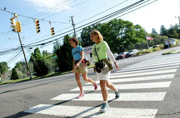 Linda Wheatley, 53, and Paula Francis, 54, of Montpelier, VT, head along Palmers Hill Road in Stamford on Sunday, Sept. 16, 2012. Francis and Wheatley left Stowe, Vermont on August 25, 2012 on a 560-mile, 44-day walk to Washington, D.C. to raise awareness about the need to adopt happiness and well-being as the ultimate goal of social and political policy. Photo: Amy Mortensen / Connecticut Post Freelance