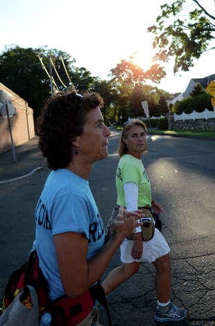 The sunrises as Paula Francis, 54, and Linda Wheatley, 53, of Montpelier, VT, walk along High Ridge Road in Stamford on Sunday, Sept. 16, 2012. Francis and Wheatley left Stowe, Vermont on August 25, 2012 on a 560-mile, 44-day walk to Washington, D.C. to raise awareness about the need to adopt happiness and well-being as the ultimate goal of social and political policy. Photo: Amy Mortensen / Connecticut Post Freelance
