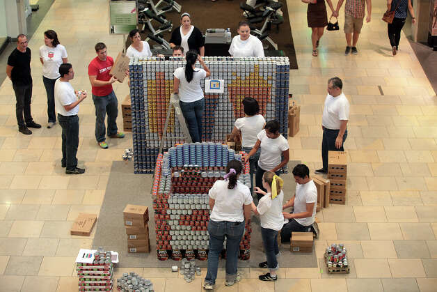 "Participants with RVK Architects with Lundy & Franke Engineering work on their entry titled, ""Drive Inn to Drive Out Hunger,"" entry at the 7th annual Canstruction at North Star Mall, Sunday, Sept. 16, 2012. The entry consisted of a movie screen and a car. Eleven teams of architects, engineers, general contractors and students used over 30,000 cans of food to create various designs. Photo: Jerry Lara, San Antonio Express-News / © 2012 San Antonio Express-News"