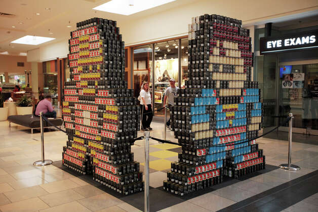 "Shoppers walk by the H-E-B Design & Construction division's ""CANtastic 4,"" entry in the 7th annual Canstruction at North Star Mall, Sunday, Sept. 16, 2012. The entry was made up of the images of super heros, Spiderman, Superman, Iron Man and Captain America. Eleven teams of architects, engineers, general contractors and students used over 30,000 cans of food to create various designs. Photo: Jerry Lara, San Antonio Express-News / © 2012 San Antonio Express-News"