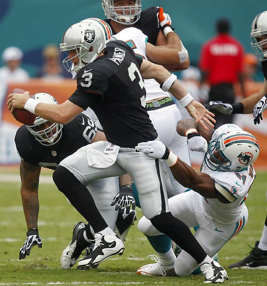 Oakland Raiders quarterback Carson Palmer (3) breaks a tackle by Miami Dolphins linebacker Cameron Wake (91) during the first half of an NFL football game on Sunday, Sept. 16, 2012, in Miami. (AP Photo/Wilfredo Lee) Photo: Wilfredo Lee, Associated Press