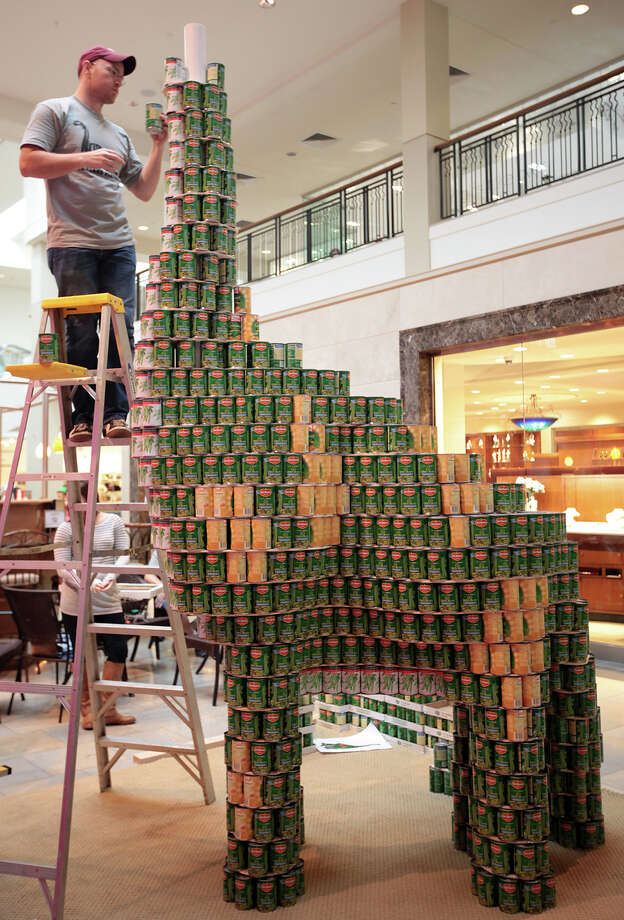 """Overland Partners' James Lancaster works on the head of """"Canosaurus,"""" an entry in the 7th annual Canstruction at North Star Mall, Sunday, Sept. 16, 2012. Eleven teams of architects, engineers, general contractors and students used over 30,000 cans of food to create various designs. The entries will be on display for two weeks and all canned good will be donated to the San Antonio Food Bank. Photo: Jerry Lara, San Antonio Express-News / © 2012 San Antonio Express-News"""