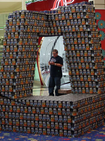 "Joe Huizar stands by the Jaster-Quintanilla San Antonio, LLP entry in the 7th annual Canstruction at North Star Mall, Sunday, Sept. 16, 2012. The piece titled ""Modern Age Towers over Hunger"" is a replica of the Central China Television Headquarters Tower. Eleven teams of architects, engineers, general contractors and students used over 30,000 cans of food to create various designs. Photo: Jerry Lara, San Antonio Express-News / © 2012 San Antonio Express-News"