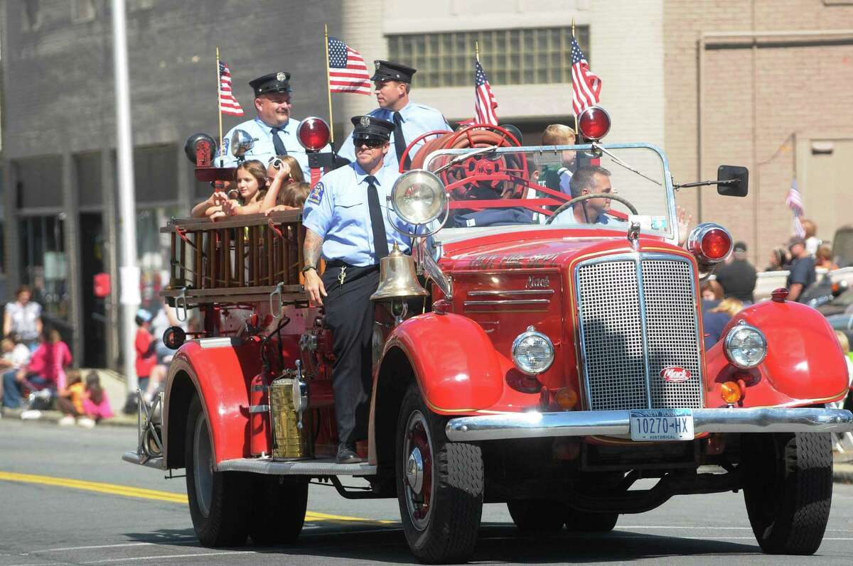 Members of the Troy Fire Department ride in an older fire truck down Fifth Avenue during the Uncle Sam Parade on Sunday, Sept. 16, 2012 in Troy, NY. (Paul Buckowski / Times Union)