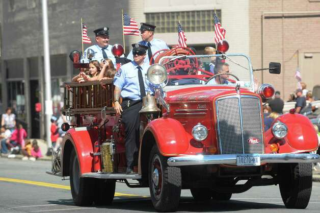 Members of the Troy Fire Department ride in an older fire truck down Fifth Avenue during the  Uncle Sam Parade on Sunday, Sept. 16, 2012 in Troy, NY.  (Paul Buckowski / Times Union) Photo: Paul Buckowski