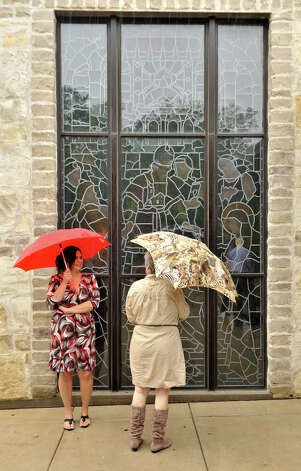 SLUG: Weather-No assignID-September 16, 2012-San Antonio, Texas---Marissa Nicholls (cq) (left) and Carol Langlinais use umbrella's to protect themselves from the rain Sunday prior to services at Holy Trinity Church. Photo: For The Express-News