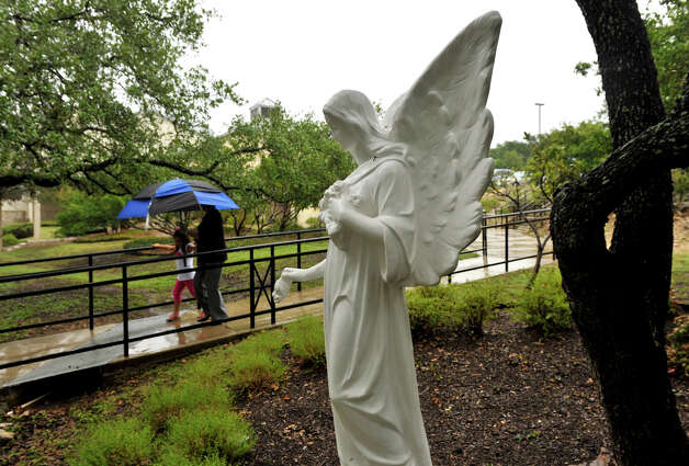 SLUG: Weather-No assignID-September 16, 2012-San Antonio, Texas---Parishoners of Holy Trinity Church use an umbrella as they walk through the rain to Sunday services. Photo: For The Express-News