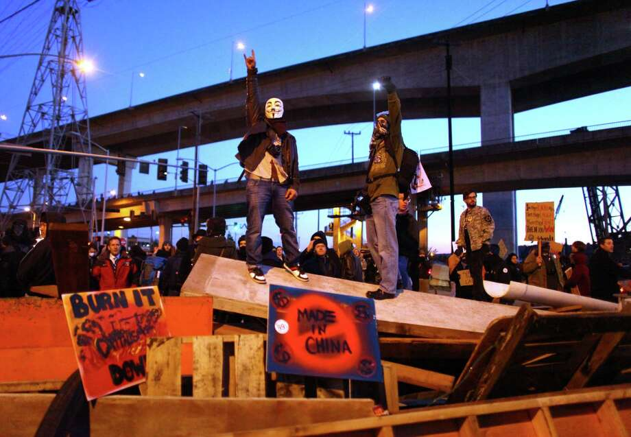 Occupy Seattle protesters stand atop a barricade on Monday, December 12, 2011 at the Port of Seattle. Hundreds of anti-Wall Street protesters gathered at the port and tried to shut down operations at the facility. Protesters scuffled with police during the rally and police used pepper spray and two flash-bang grenades to disperse the crowd after one protester threw a lit road flare toward officers. Other protesters tossed red paint on officers. Photo: JOSHUA TRUJILLO / SEATTLEPI.COM