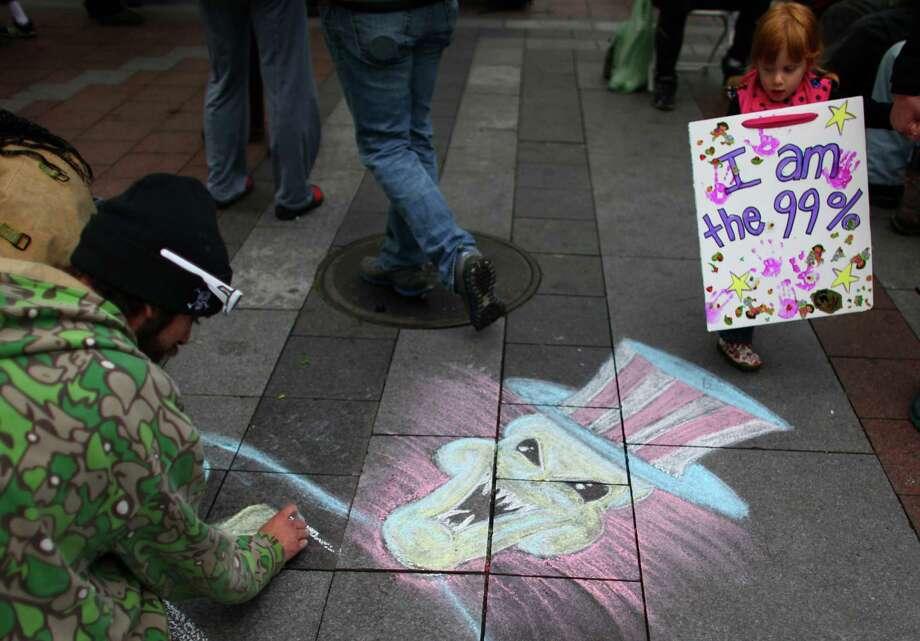 Mercedes Huddleston, 3, walks past chalk art during an Occupy Seattle protest at Westlake Park on Friday, October 7, 2011. Photo: JOSHUA TRUJILLO / SEATTLEPI.COM