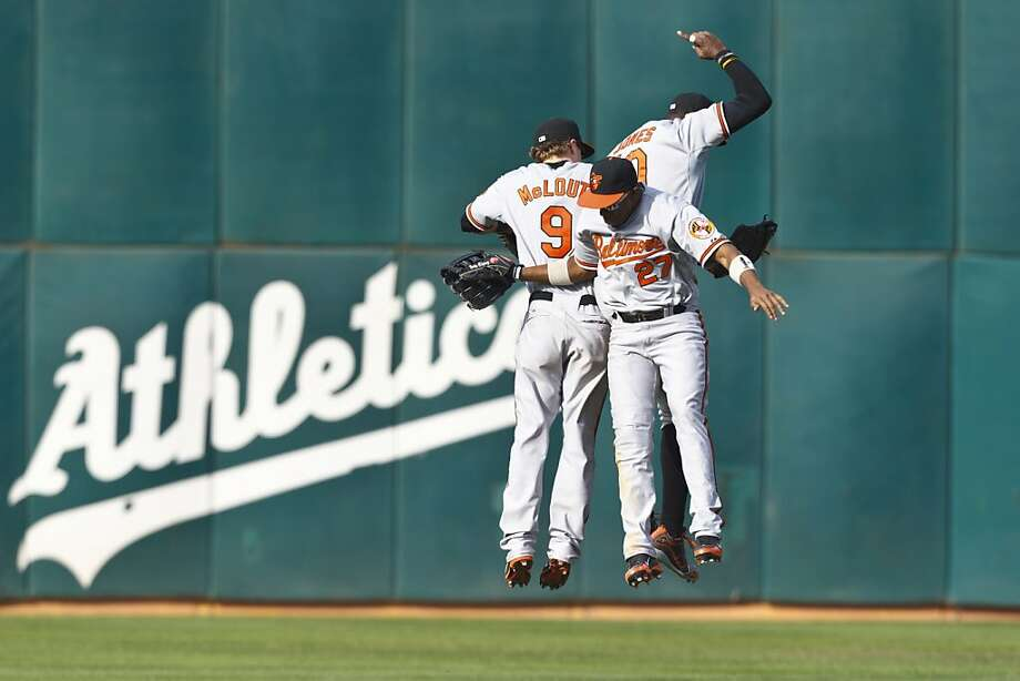Endy Chavez #27 of the Baltimore Orioles, Nate McLouth #9, and Adam Jones #10 celebrate after the game against the Oakland Athletics at O.co Coliseum on September 16, 2012 in Oakland, California. The Baltimore Orioles defeated the Oakland Athletics 9-5. (Photo by Jason O. Watson/Getty Images) Photo: Jason O. Watson, Getty Images