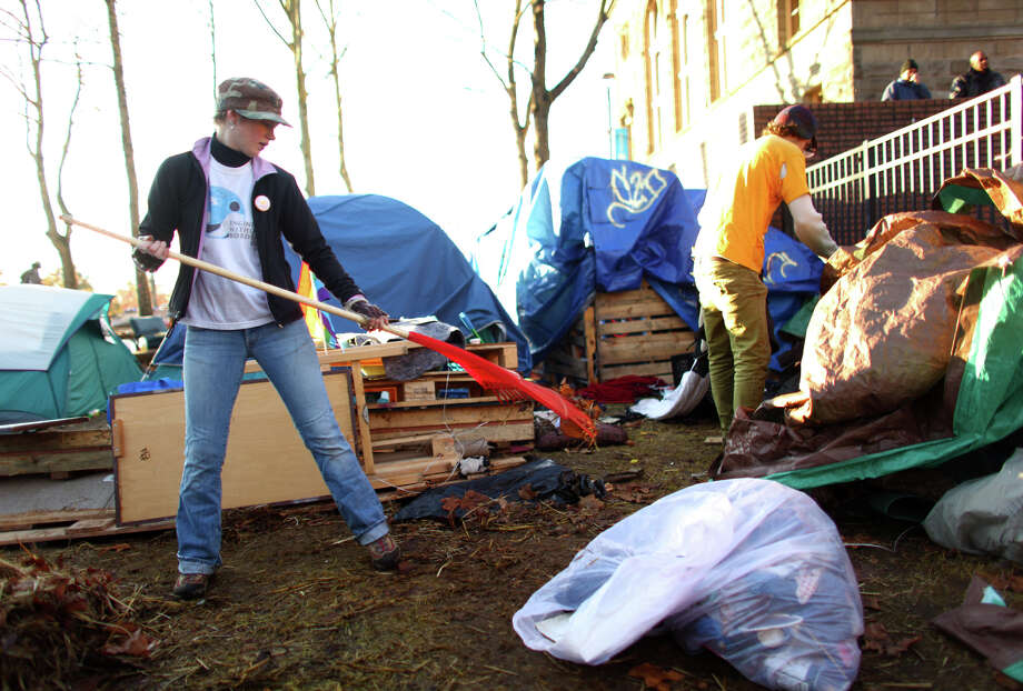 "Protesters work to clean up trash as the Occupy Seattle camp is disassembled on Friday, December 9, 2011 at Seattle Central Community College. Friday was the deadline for the protest camp to vacate the college campus in Seattle's Capitol Hill neighborhood. Many campers left but some remained in the camp. ""Now we can concentrate on the movement instead of camping and surviving,"" said protester Marissa Adams. She said the cold temperatures and basic survival and safety of protesters have taken a significant amount of the movement's focus. Many at the camp said at the time that come spring, a camp would likely return. Photo: JOSHUA TRUJILLO / SEATTLEPI.COM"