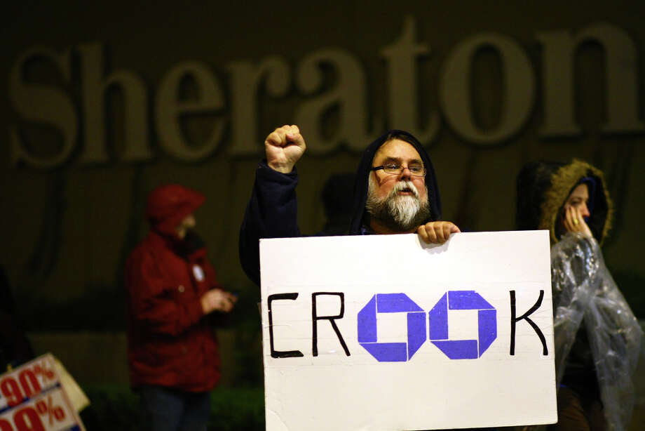 A protester holds a sign in front of the Sheraton Hotel during an Occupy Seattle protest where Chase Bank CEO Jamie Dimon was speaking on Wednesday, November 2, 2011. A few hundred people tried to block the doors to the hotel during the event hosted by the University of Washington business school. Photo: JOSHUA TRUJILLO / SEATTLEPI.COM