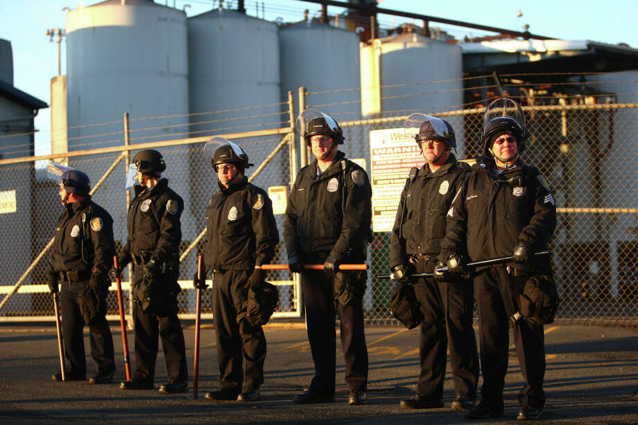 Officers guard a gate on Monday, December 12, 2011 at the Port of Seattle. Hundreds of anti-Wall Street protesters gathered at the port and tried to shut down operations. Protesters scuffled with police during the rally and police used pepper spray and two flash-bang grenades to disperse the crowd after a protester threw a lit road flare toward officers. Another threw red paint on officers. Photo: JOSHUA TRUJILLO / SEATTLEPI.COM