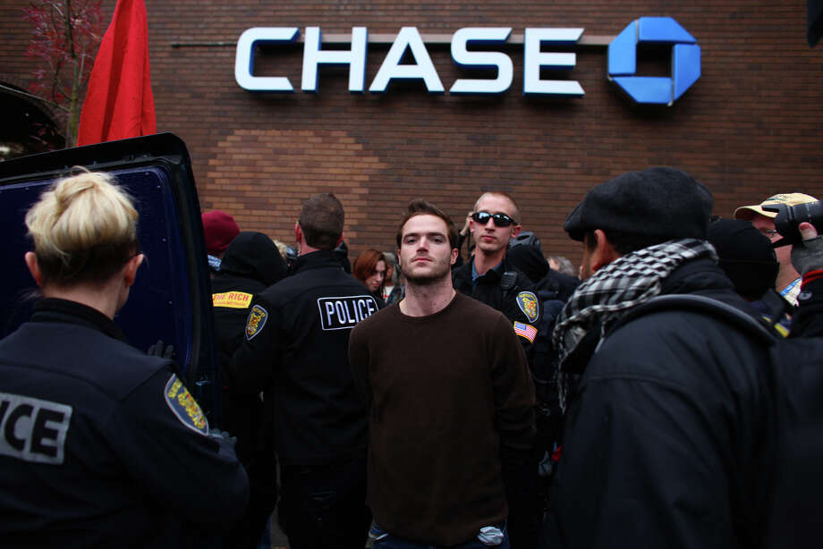 A man is arrested after being removed from a bank during an Occupy Seattle protest outside a Chase branch on Broadway Avenue East and East Thomas Street on Wednesday, November 2, 2011 in Seattle. Protesters connected themselves together with pipes and locks inside the branch. When they were removed from the bank a melee ensued as police worked to keep back protesters. Chase CEO Jamie Dimon spoke later in the day at an event in Downtown Seattle. Photo: JOSHUA TRUJILLO / SEATTLEPI.COM