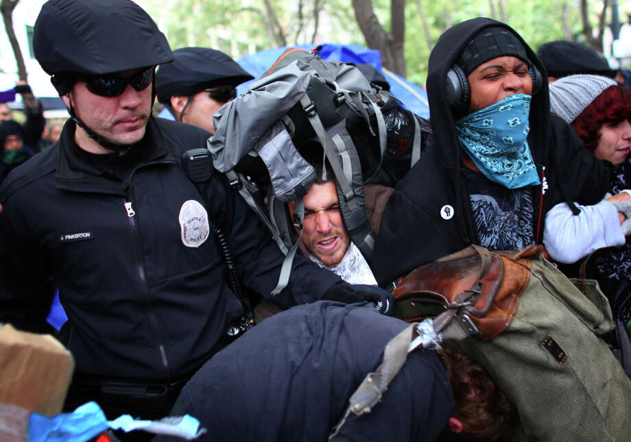During a brief shoving match a man becomes tangled in his backpack during the Occupy Seattle protest at Westlake Park on Wednesday, October 5, 2011 in Seattle. Protesters were ordered to remove their encampment from the park, leading to arrests of people that refused to move. Photo: JOSHUA TRUJILLO / SEATTLEPI.COM
