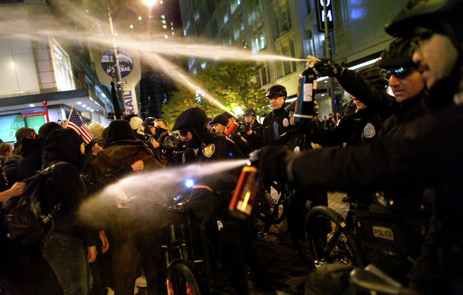 Seattle Police officers deploy pepper spray into a crowd during an Occupy Seattle protest on Tuesday, November 15, 2011 at Westlake Park. Protesters gathered in the intersection of 5th Avenue and Pine Street after marching from their camp at Seattle Central Community College in support of Occupy Wall Street. Many refused to move from the intersection after being ordered by police. Police then began spraying into the gathered crowd hitting dozens of people. An 84 year-old activist was hit with spray during the chaos. Photo: JOSHUA TRUJILLO / SEATTLEPI.COM