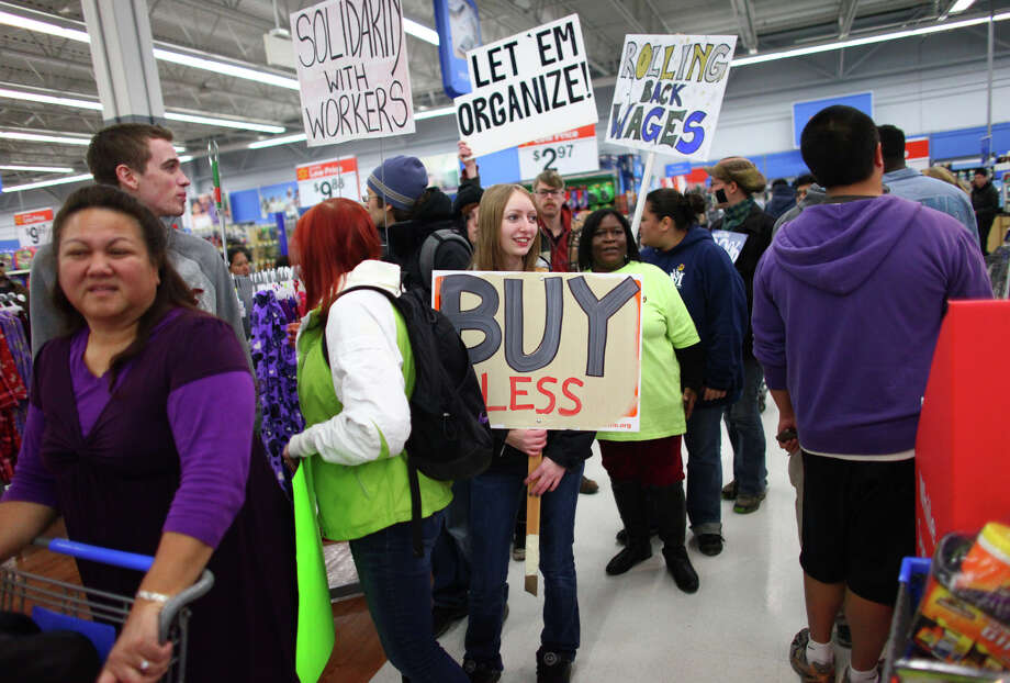 Protesters march through Walmart in Renton during an Occupy Seattle protest at the retailer on Friday, November 25, 2011. A few dozen protesters gathered in front of the store and briefly marched through the store during the Black Friday protest. Photo: JOSHUA TRUJILLO / SEATTLEPI.COM