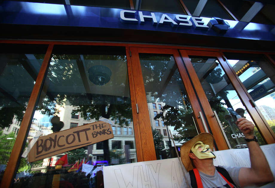 A sign in affixed to the Chase Bank branch of 4th Avenue on Saturday, October 15, 2011 in Seattle as about 5,000 people joined protesters that were camped at Westlake Park for two weeks. Photo: JOSHUA TRUJILLO / SEATTLEPI.COM