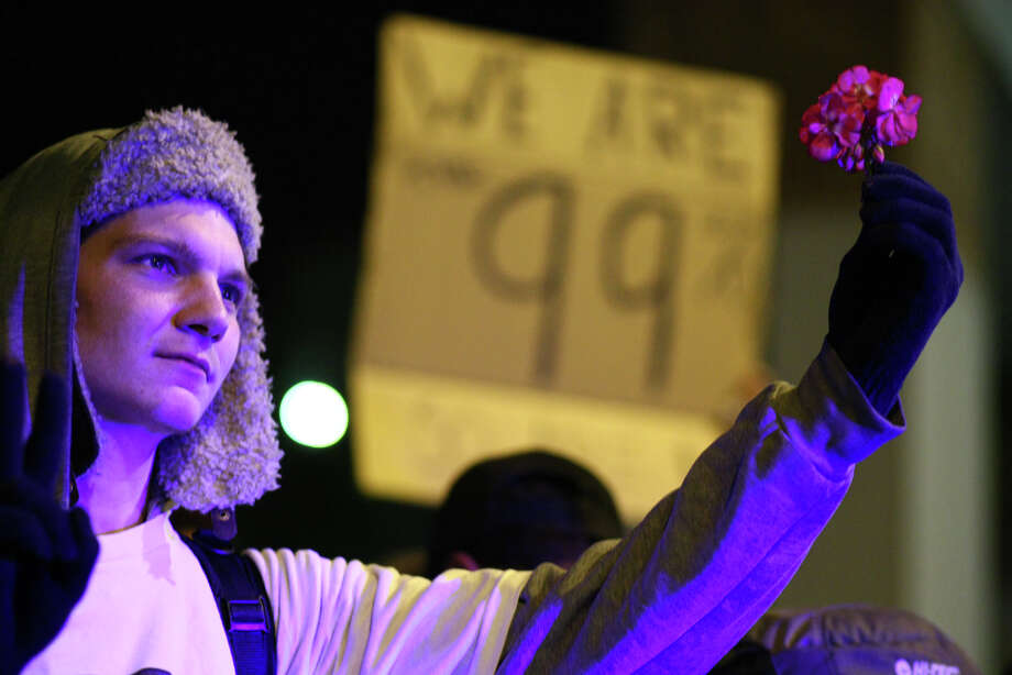 An Occupy Seattle demonstrator holds a flower while illuminated by police lights at Westlake Park. Photo: JOSHUA TRUJILLO / SEATTLEPI.COM