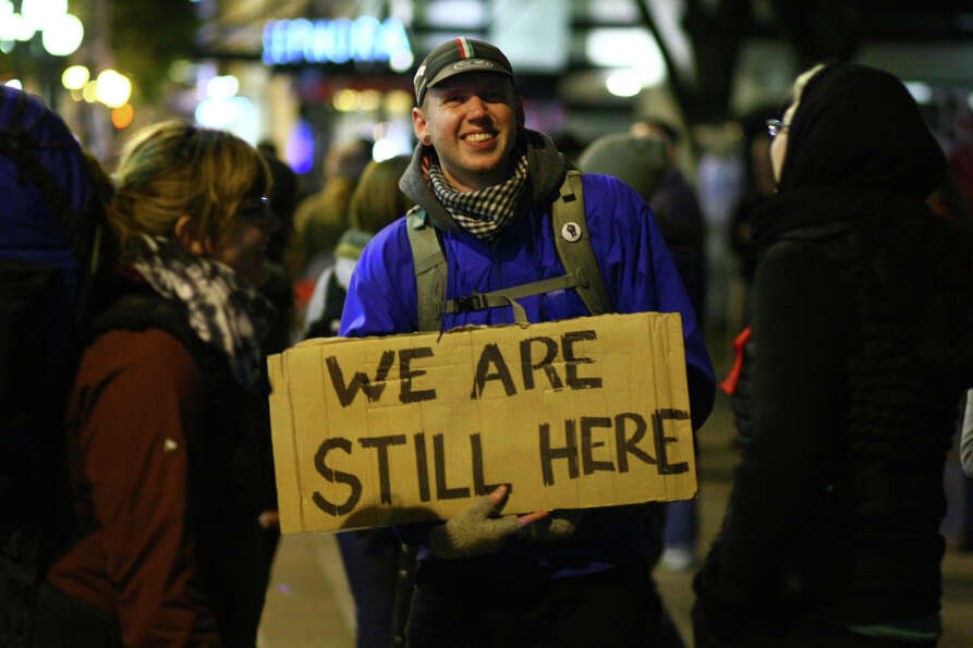 An Occupy Seattle demonstrator holds a sign at Westlake Park on Wednesday, October 12, 2011 in Seatt
