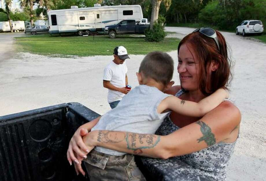 Nicole Garcia hugs her son, Johnny Joe Garcia, III, 3, at the Tips Park in Three Rivers, Texas, Monday, March 26, 2012. In back is her husband, Johnny Joe Garcia, Jr. The family has lived at the park for the past two months. He is a pipeline trucker. Jerry Lara/San Antonio Express-News