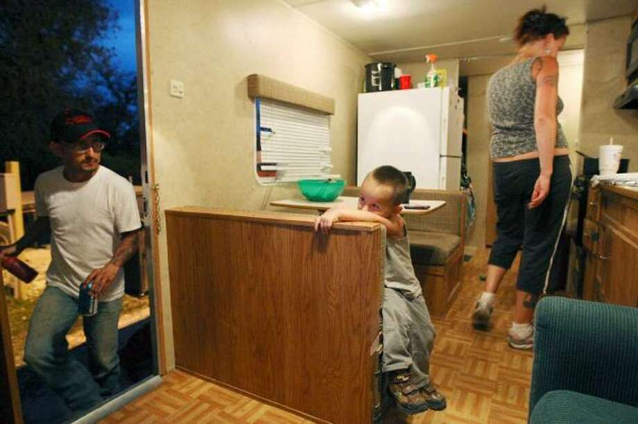 Three-year-old J.J. Garcia, III, waits watching television while the family prepares for dinner at Tips Park in Three Rivers, Texas, Wednesday, March 29, 2012. Johnny Garcia, Jr., left, logs over 300 miles a day as a pipeline truck driver and his wife, Nicole, stays at home to take care of their son. He has been working oilfield related trucking on and off since 2007. The couple bought the travel trailer in Asherton and have lived at the park for over two months. Jerry Lara/San Antonio Express-News
