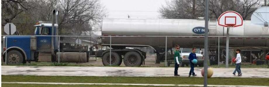 Students from McMullen County Elementary School in Tilden, Texas play ball Wednesday February 15, 2012 as a tanker truck passes by the school's playground. The McMullen County Independent School District is in the Eagle Ford shale formation area and enrollment in the district has seen an increase of 27 percent as people come looking for jobs related to the oil and gas industry. Truck traffic in the small town has also increased dramatically. John Davenport/San Antonio Express-News