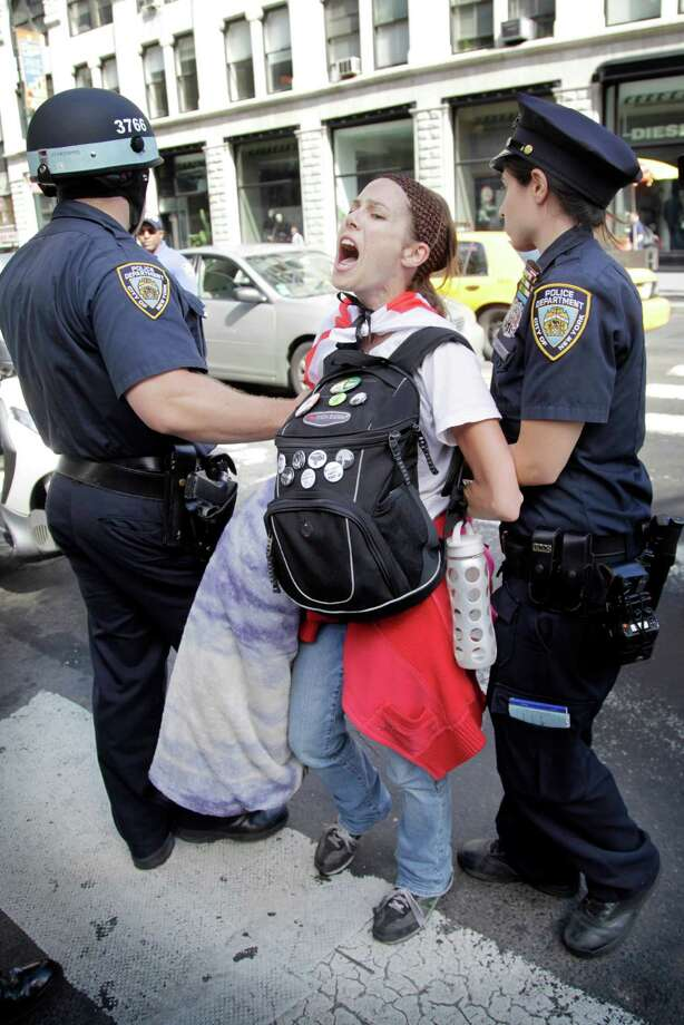 An activist associated with the Occupy Wall Street movement is taken into custody during a march in New York, Sunday, Sept. 16, 2012. The Occupy Wall Street movement will mark its first anniversary on Monday. (AP Photo/Seth Wenig) Photo: Seth Wenig
