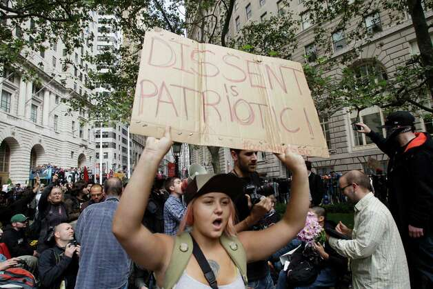 FILE - In this Sept. 17, 2011 file photo, a woman in the crowd displays a sign as demonstra