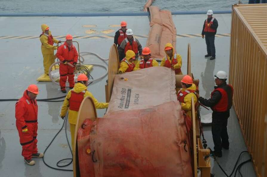 Workers unroll inflatable boom and fill it before casting it off into Valdez waters during oil spill