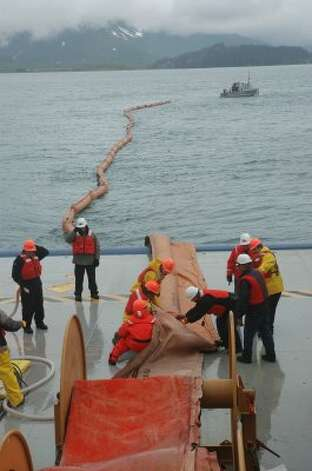 Workers unroll inflatable boom and fill it before casting it off into Valdez waters during oil spill response training for Shell. The inflatable boom in the water is being pulled by an oil spill response vehicle -- one of three that can be housed on the Nanuq when not in operation. (Jennifer A. Dlouhy / The Houston Chronicle)