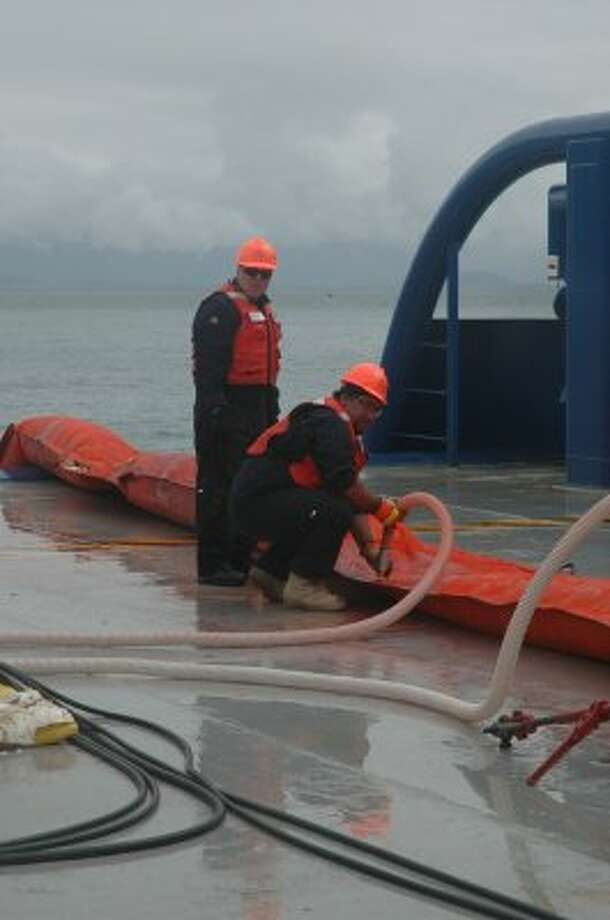 Workers fill inflatable boom with air before casting it off into Valdez waters during oil spill response training for Shell. (Jennifer A. Dlouhy / The Houston Chronicle)