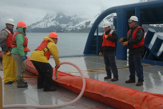 Workers unroll inflatable boom and fill it before casting it off into Valdez waters during oil spill response training for Shell. (Jennifer A. Dlouhy / The Houston Chronicle)