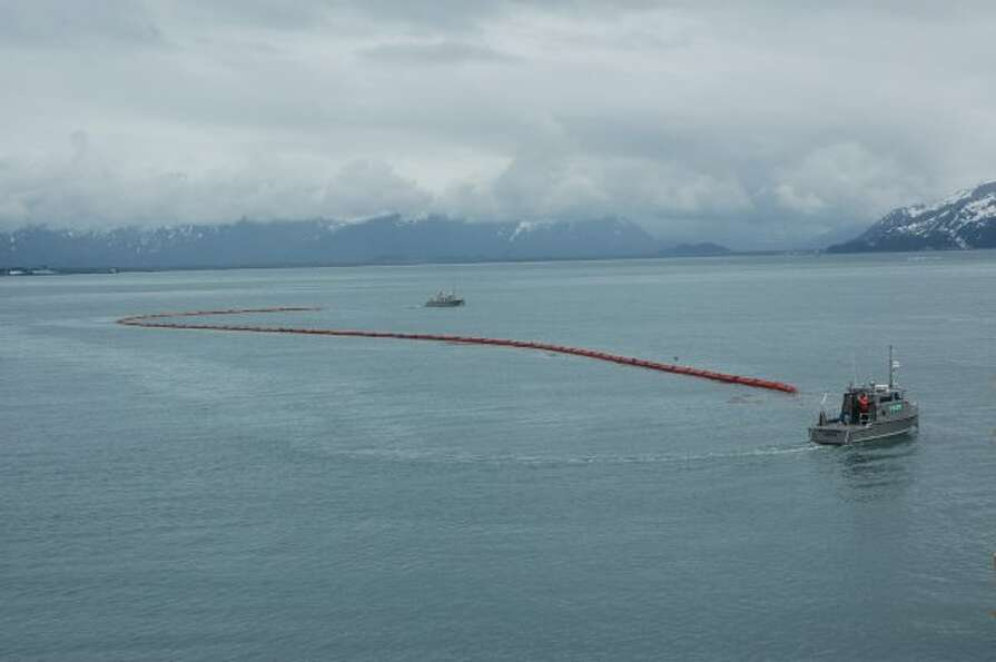 Inflatable boom stretches between two oil spill response vehicles in Valdez waters during a Shell tr