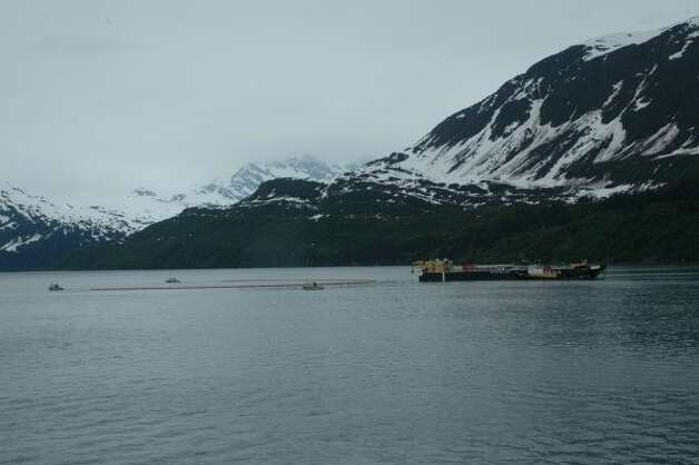 Inflatable boom is deployed in a U shape in Valdez waters during Shell's oil spill response training in Alaska. Workers on a skimmer-equipped barge in the center practice sucking up pooled oil. (Jennifer A. Dlouhy / The Houston Chronicle)