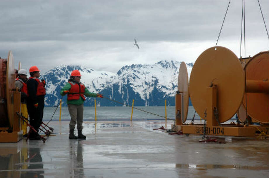 Priscilla Ridley holds a rope before equipment is hoisted on Shell's Nanuq oil recovery and supply vessel, during oil spill response training in Valdez, Alaska. The Chugagh Mountains are in the background. (Jennifer A. Dlouhy / The Houston Chronicle)