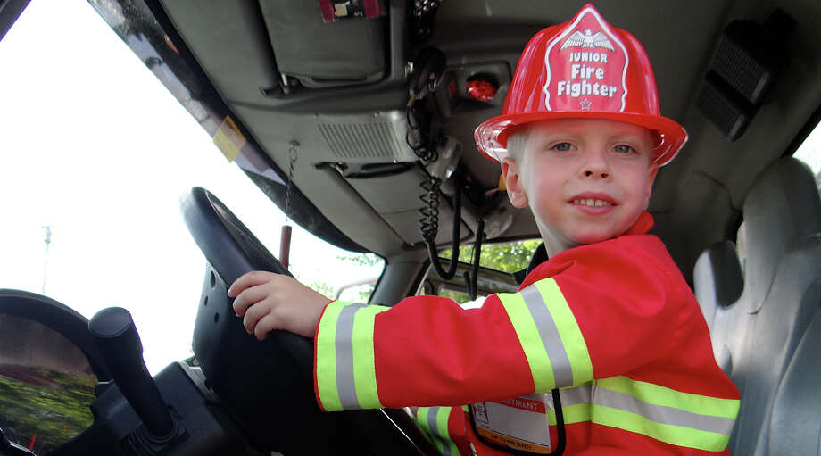 Liam Sikora, 3, of Fairfield, takes on wheel of a fire truck -- Southport Volunteer Fire Department's Squad 14 truck -- at Sunday''s Touch-a-Truck event sponsored by the Junior Woman's Club of Fairfield. Photo: Mike Lauterborn / Fairfield Citizen contributed
