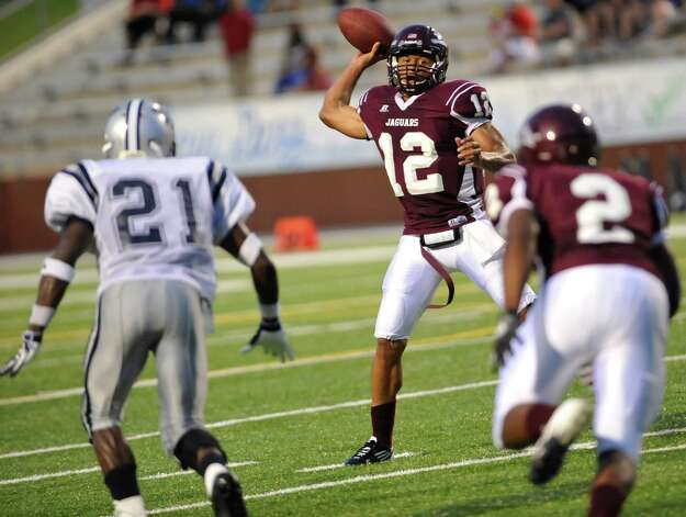 "Central's #12, Robert Mitchell, looks for one of his receivers as WO-S #21, Colin Janice, is headed straight for him.  The West Orange-Stark football team played Central Medical Magnet High School Friday night, September 14, 2012 at the Carrol A. ""Butch"" Thomas Educational Support Center. At the half, WO-S was ahead 7-0. This is a nondistrict game.  Dave Ryan/The Enterprise Photo: Dave Ryan"