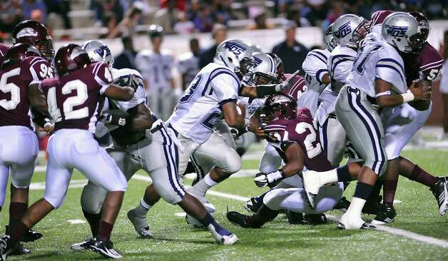 "WO-S #23, Ar'Tevin McDonald, center, bolts through a hole his offensive teammates made for him. The West Orange-Stark football team played Central Medical Magnet High School Friday night, September 14, 2012 at the Carrol A. ""Butch"" Thomas Educational Support Center. At the half, WO-S was ahead 7-0. This is a nondistrict game.  Dave Ryan/The Enterprise Photo: Dave Ryan"