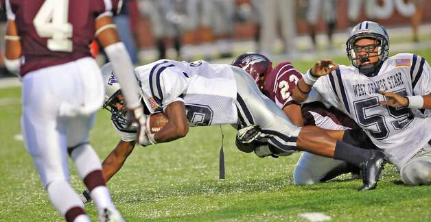 "WO-S #39, John Scott, left, holds tight to the ball as Central #31, , looks for an open receiver  while Central # 23, Trent Samuels tries to bring him down. The West Orange-Stark football team played Central Medical Magnet High School Friday night, September 14, 2012 at the Carrol A. ""Butch"" Thomas Educational Support Center. At the half, WO-S was ahead 7-0. This is a nondistrict game.  Dave Ryan/The Enterprise Photo: Dave Ryan"