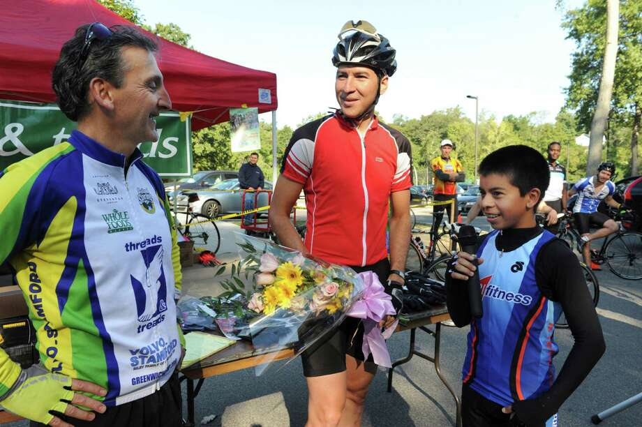 From left, Mickey Yardis, the owner of Threads and Treads, Cristian Velasquez, of Greenwich, the winner of the Tour de Greenwich XXVIII, and Velasquez's translator Jonathan Guiza, 14, talk after the race Sunday, Sept. 16, 2012. Photo: Helen Neafsey / Greenwich Time