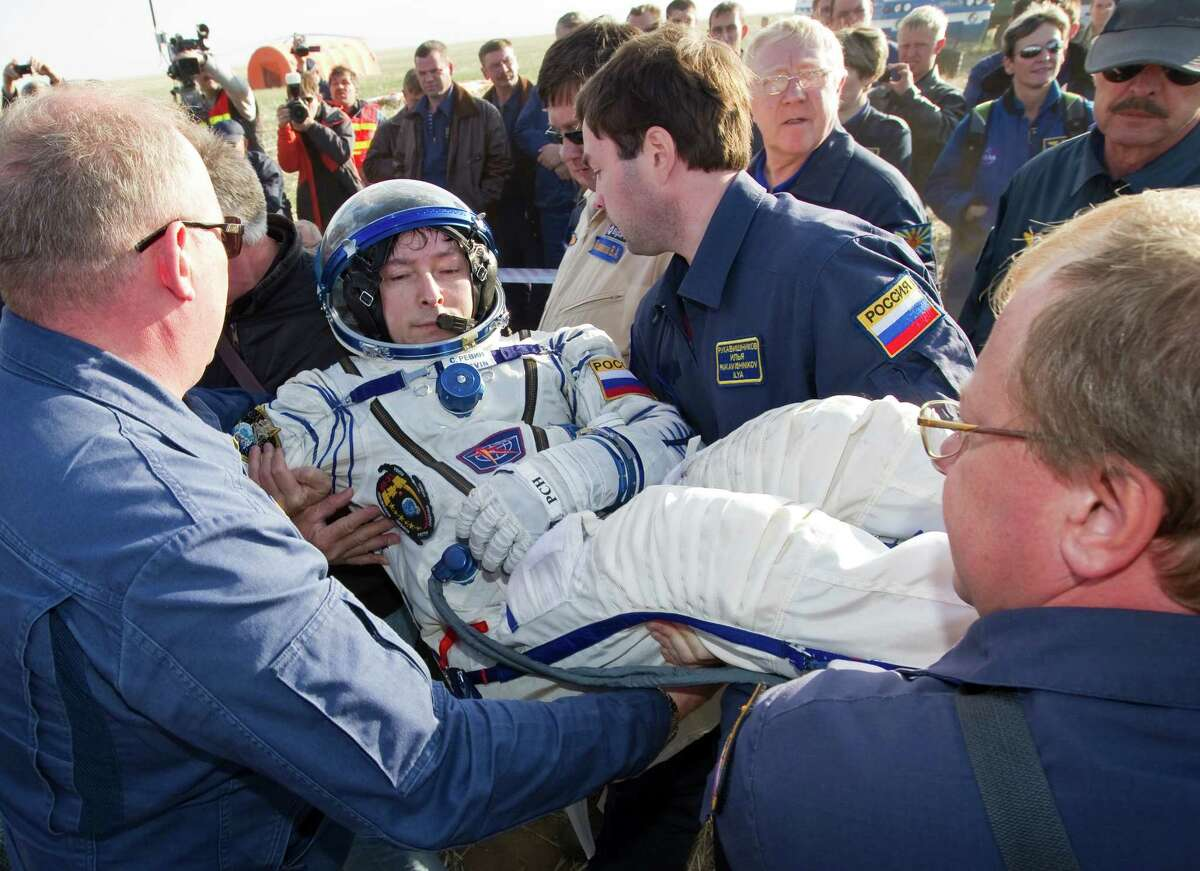 Ground personnel assist International Space Station (ISS) crew member Russian cosmonaut Sergei Revin outside the Soyuz TMA-04M capsule shortly after the landing near the town of Arkalyk in northern Kazakhstan, on September 17, 2012. A woman took today command of the ISS for only the second time as three US and Russian colleagues made a safe return from the orbiting space lab to the Kazakh steppe. AFP PHOTO / POOL/ SHAMIL ZHUMATOVSHAMIL ZHUMATOV/AFP/GettyImages