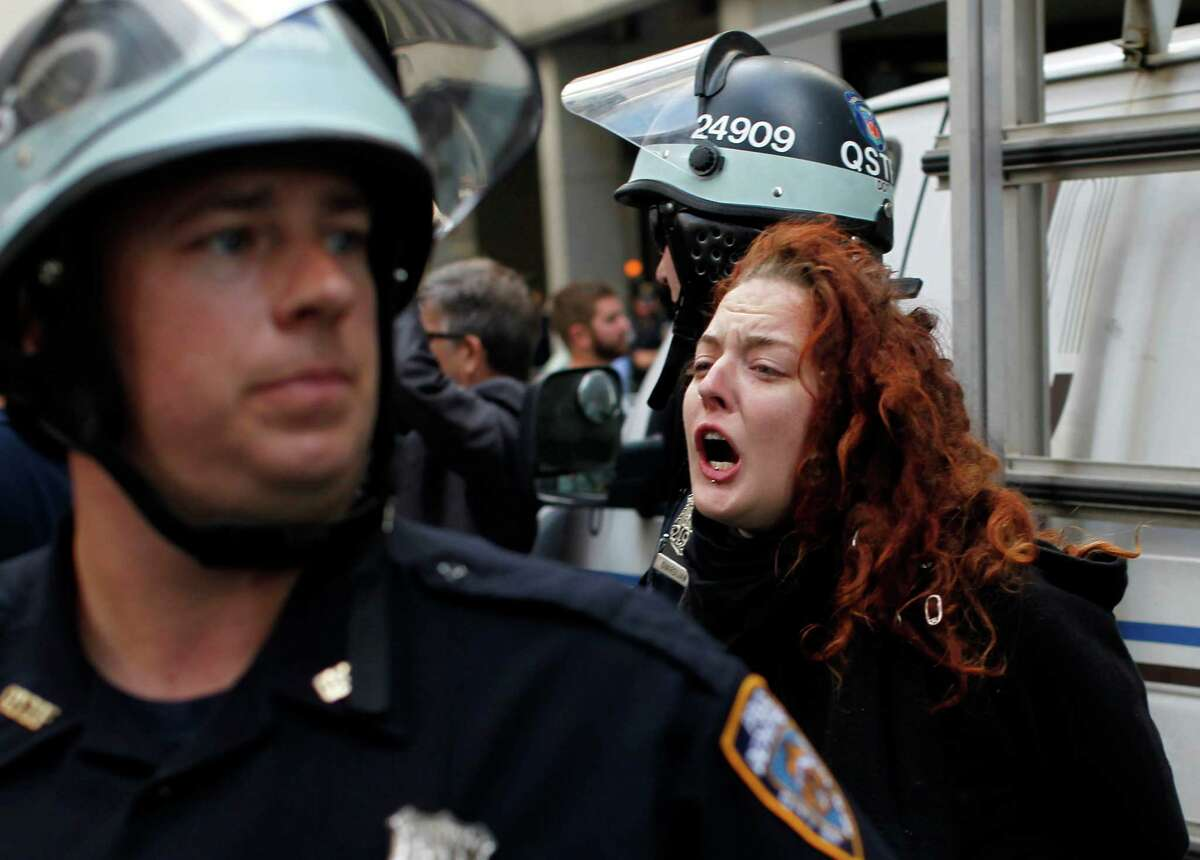 A woman yells out while being arrested during an Occupy Wall Street march, Monday, Sept. 17, 2012, in New York. A handful of Occupy Wall Street protestors were arrested during a march on the New York Stock Exchange on the anniversary of the grass-roots movement.