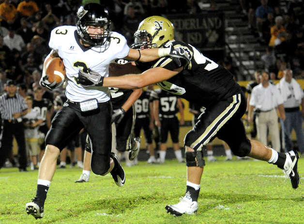 Vidor's Bryce Cooper carries the ball as Nederland's Corbin Carr moves in for the tackle at Bulldog Stadium in Nederland, Friday, September 23, 2011   Tammy McKinley/The Enterprise Photo: TAMMY MCKINLEY