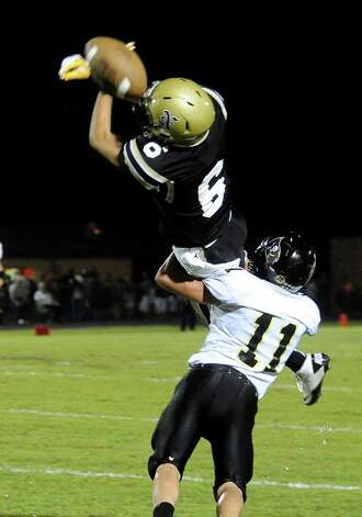 The ball slips through the fingers of Nederland's Daniel Atterberry as Vidor's Quentin Whitmire makes the hit at Bulldog Stadium in Nederland, Friday, September 23, 2011   Tammy McKinley/The Enterprise Photo: TAMMY MCKINLEY