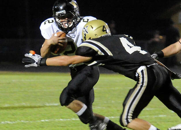 Vidor's David Bolinger runs the ball as Nedderland's Seth Barrow moves in for the tackle at Bulldog Stadium in Nederland, Friday, September 23, 2011   Tammy McKinley/The Enterprise Photo: TAMMY MCKINLEY