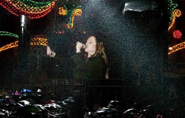 "People watch mexican singer Jenni Rivera  under  heavy rain on a giant TV screen during the traditional ""El Grito,"" or shout, to kick off Independence Day celebrations at the Zocalo in Mexico City, late Saturday, Sept. 15, 2012. Mexico is marking the 202st anniversary of the ""Grito de Dolores,"" honoring the call to arms made by the priest Miguel Hidalgo in 1810 that began the struggle for independence from Spain, achieved in 1821. (AP Photo/Eduardo Verdugo) Photo: Eduardo Verdugo, Associated Press"