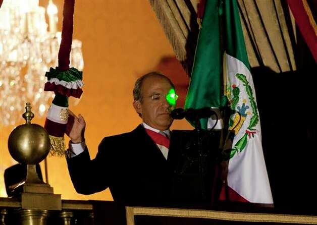 "A green laser light reflects on President Felipe Calderon's face at the balcony of the National Palace during the traditional ""El Grito,"" or shout, to kick off Independence Day celebrations at the Zocalo in Mexico City, late Saturday, Sept. 15, 2012. Mexico is marking the 202st anniversary of the ""Grito de Dolores,"" honoring the call to arms made by the priest Miguel Hidalgo in 1810 that began the struggle for independence from Spain, achieved in 1821. (AP Photo/Eduardo Verdugo) Photo: Associated Press"
