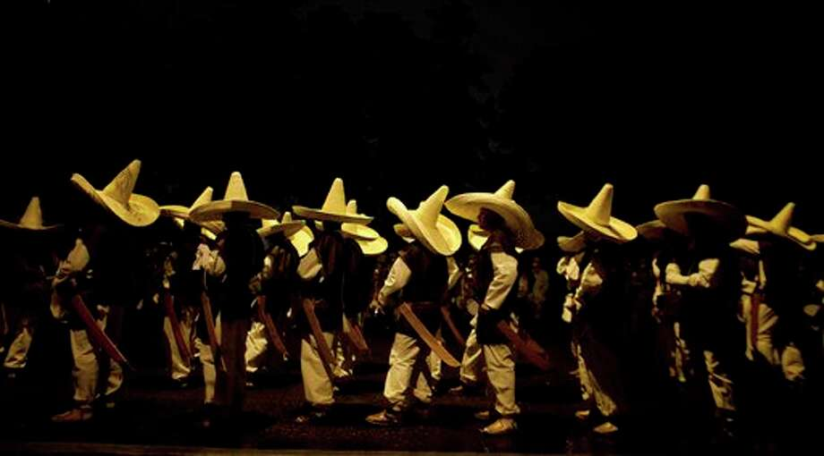 Members of the military wearing costumes representing the 1911 revolutionary forces, stand at a military base moments before leaving to downtown Mexico City for to the military parade of the Independence Day celebrations, Mexico City, Sunday Sept. 16, 2012. Mexico celebrates the 202nd anniversary of its 1810 independence uprising. (AP Photo/Alexandre Meneghini) Photo: Associated Press